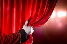 stock-photo-10348904-usher-opening-red-theater-curtain-with-spotlights